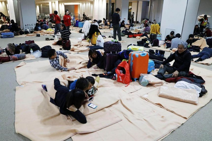Passengers rest after flight operations were suspended, due to by heavy snowfall, at New Chitose Airport in Chitose, Hokkaido, northern Japan, on Jan 5, 2019.