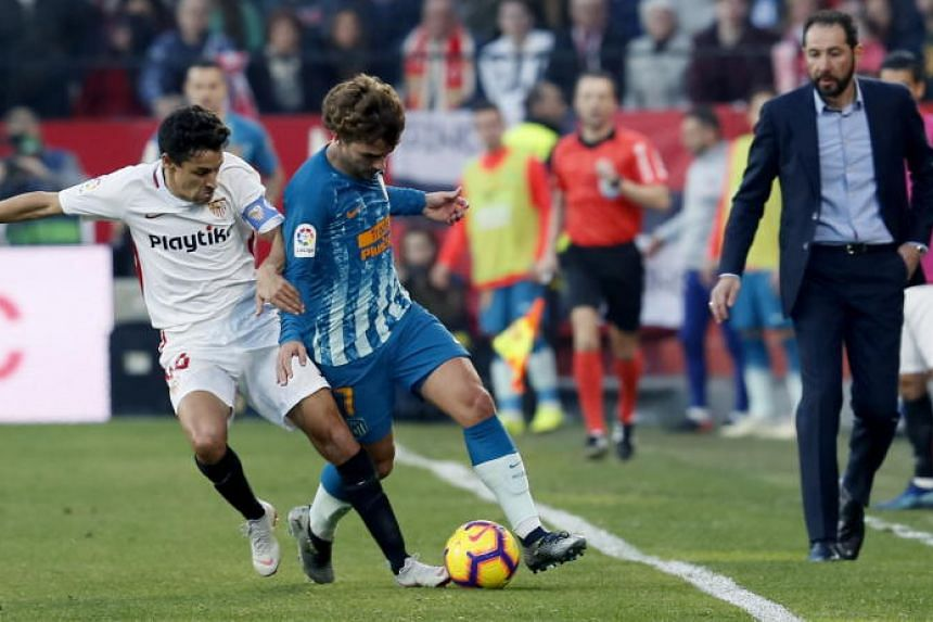 Sevilla's defender Jesus Navas (left) vies for the ball against Atletico's forward Antoine Griezmann (second from left) during the Spanish La Liga match between Sevilla and Atletico Madrid at Ramon Sanchez Pizjuan stadium in Seville, Andalusia, Spain
