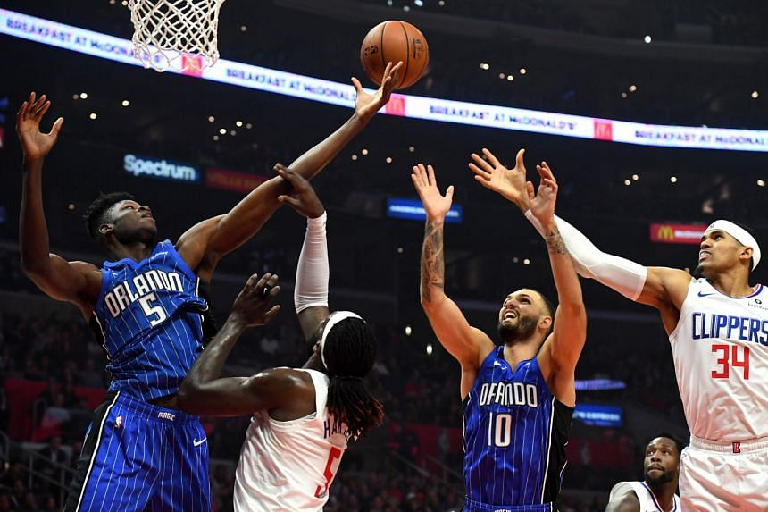 Orlando Magic centre Mo Bamba (5), guard Evan Fournier (10), and Los Angeles Clippers forward Montrezl Harrell (5) and forward Tobias Harris (34) all go for a rebound in the first half of the game.