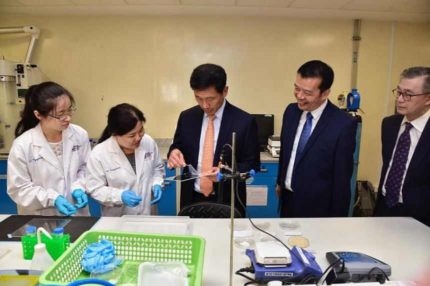 (From left)  PhD student Cui Xi with research fellow Zhao Guili look on as Minister for Education, Ong Ye Kung, holds on to a biodegradable packaging film. He is accompanied by Director of Food Science & Technology Programme William Chen and Director