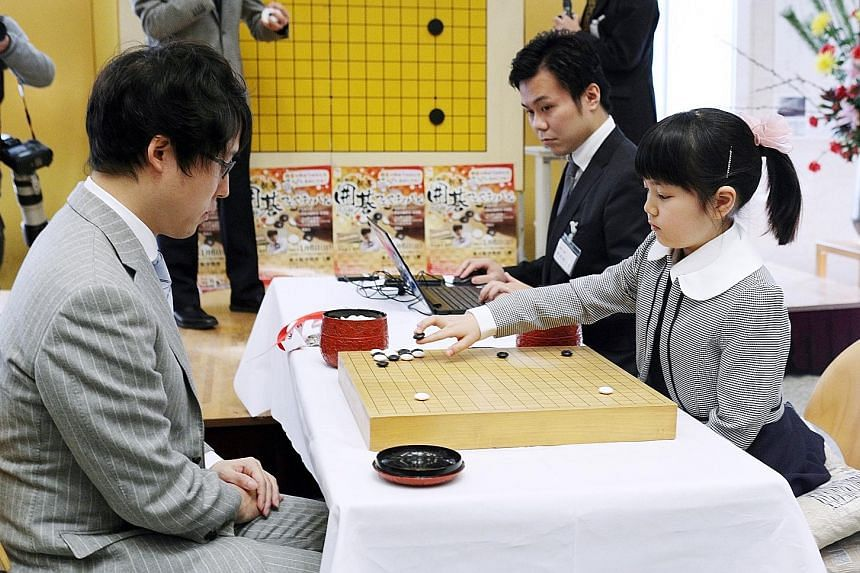 Sumire Nakamura playing against Mr Yuta Iyama in Osaka on Sunday. Sumire started playing Go with her father, national champion Shinya Nakamura, when she was three.