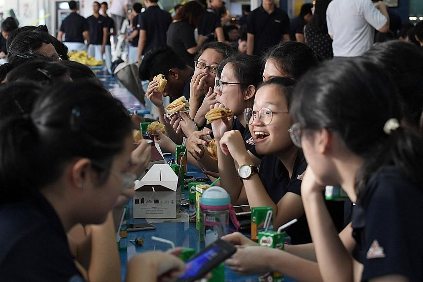 Clockwise from far left: TMJC student Clement Choo giving an apple to teacher Yeo-Chen Zhiling as a sign of appreciation; the school's friendly football match; and students having breakfast yesterday.