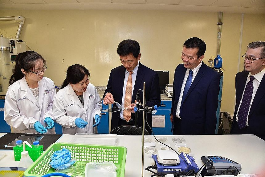 Minister for Education Ong Ye Kung (centre) examining a biodegradable cellulose film packaging in the laboratory with (from left) PhD student Cui Xi; research fellow Zhao Guili; Professor William Chen, director of NTU's Food Science and Technology pr