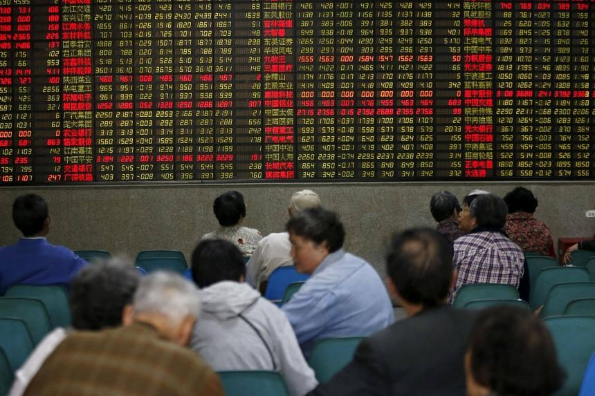 Investors looking at an electronic board showing stock information at a brokerage house in Shanghai, China.