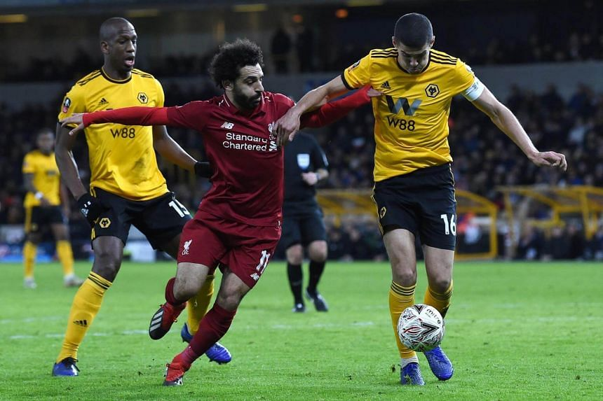 Liverpool's Egyptian midfielder Mohamed Salah (centre) vies with with Wolverhampton Wanderers' French defender Willy Boly (left) and English midfielder Conor Coady during the English FA Cup third round football match at the Molineux stadium in Wolver