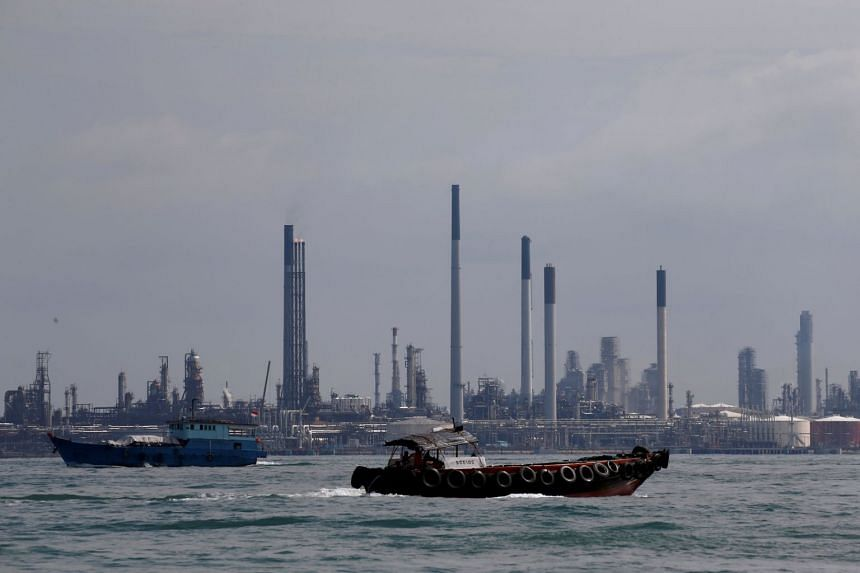 Boats sailing past the Pulau Bukom oil refinery. Shell Eastern Petroleum, which carries out refinery works at the facility, was fined $400,000 for an offence under the Workplace Safety and Health Act on Jan 8, 2019.