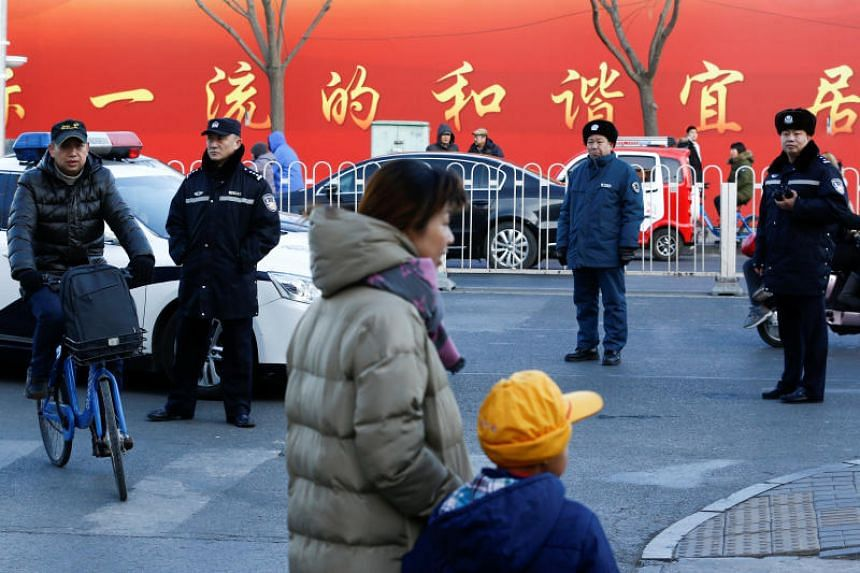 Police watch as a woman and a child leave a primary school that was the scene of an attack in Beijing.