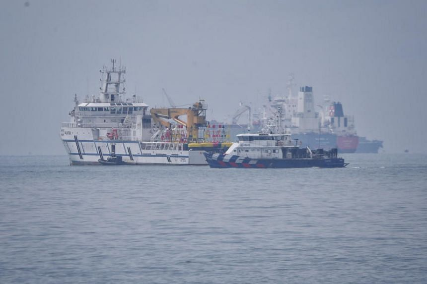 A Singapore Police Coast Guard vessel (centre) passes a Malaysian government vessel (left) in the waters between Singapore and Malaysian on Dec 6, 2018.