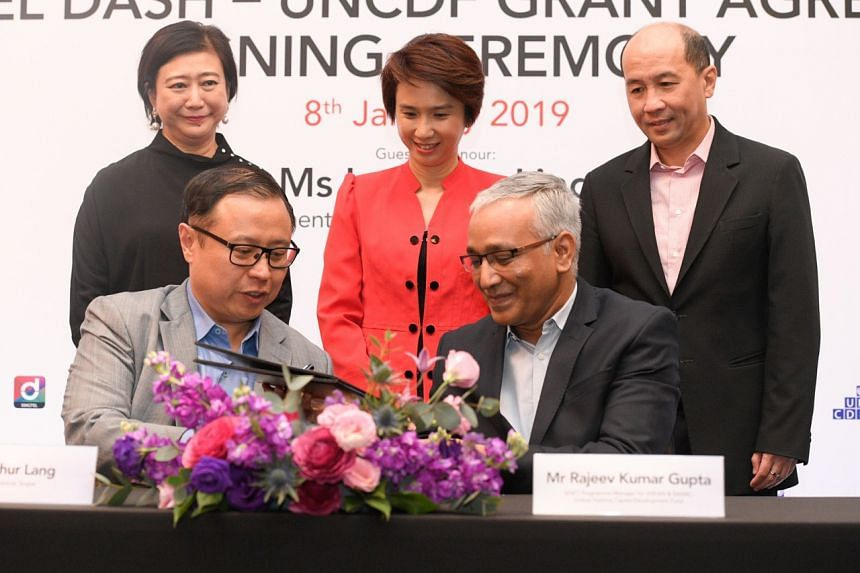 Mr Arthur Lang, Singtel's International Group chief executive and Mr Rajeev Gupta, the United Nations Capital Development Fund's Shift programme manager for Asean and Saarc, sign a grant agreement on Jan 8, 2019.