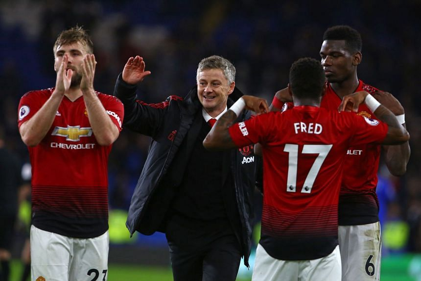 United's Norwegian caretaker manager Ole Gunnar Solskjaer celebrates with players after a match.