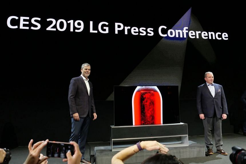 David VanderWaal (left), LG US' senior vice-president of marketing and Tim Alessi, LG US' senior director of home entertainment product marketing, showing off the Signature Oled TV R rollable TV during a press conference at Las Vegas on Jan 7, 2019.