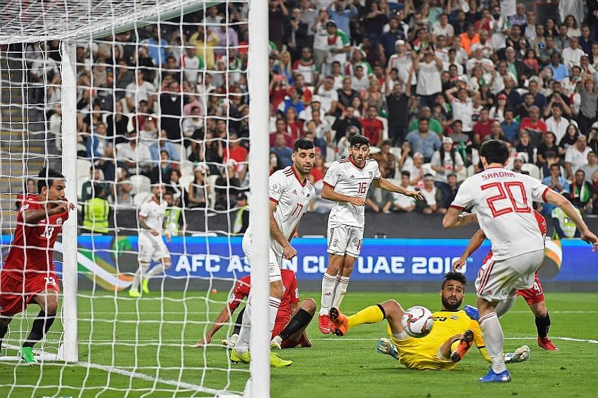 Top: The Yemen defence is all at sea as Iran forward Sardar Azmoun scored the fourth goal in their 5-0 win at the Mohammed Bin Zayed stadium in Abu Dhabi on Monday. Above: Iraq defender Ali Adnan celebrating his late free-kick goal which turned out t