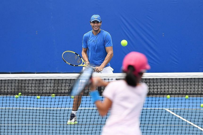 Rafael Nadal of Spain hitting with a young player from his academy in Brisbane last Saturday before his withdrawal. But he did not feel pain during a Sydney exhibition match yesterday.
