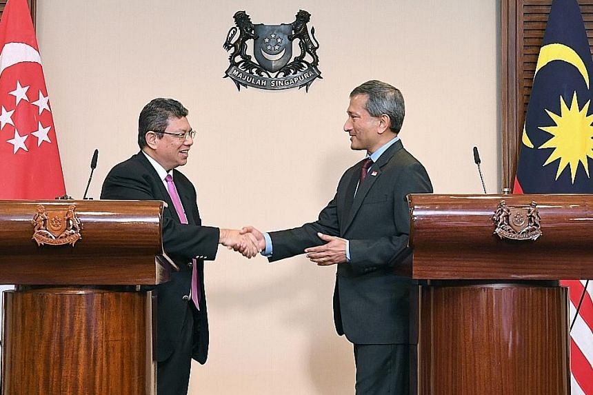 Foreign Minister Vivian Balakrishnan and his Malaysian counterpart Saifuddin Abdullah ending their joint press conference with a warm handshake, after their meeting in Singapore yesterday.