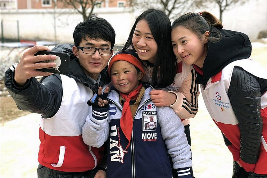 Volunteers having a wefie taken with Wang Fuman. Thanks to donations and government aid, the boy and his family have moved out from an old mud hut into a new house just a 10-minute walk from school.