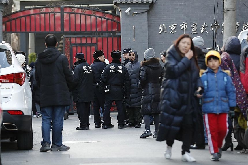Police and parents outside the school in Beijing yesterday where a man had earlier attacked pupils with a hammer. The attacker has been detained by police.
