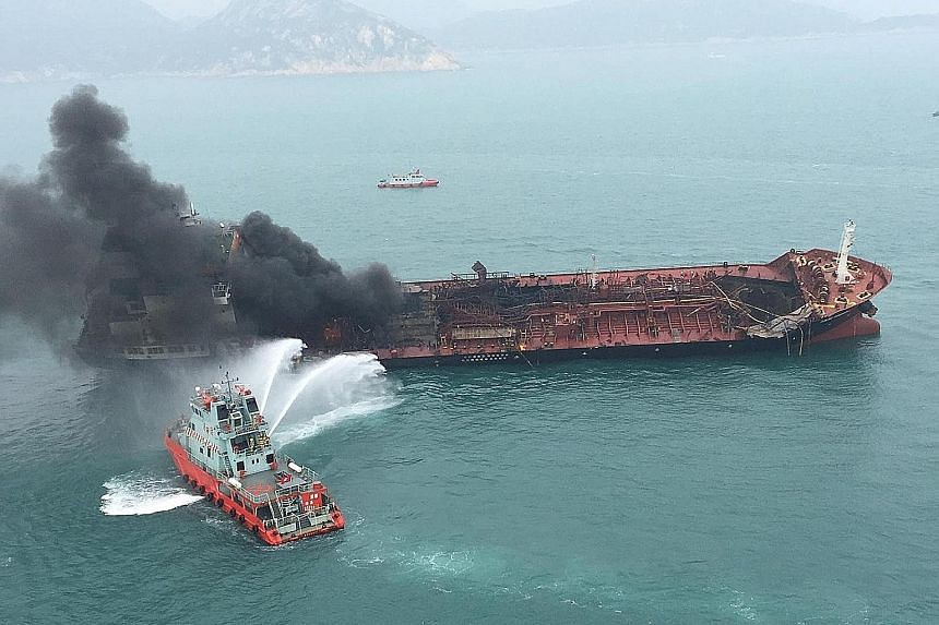 The Aulac Fortune in the waters off Hong Kong yesterday. The vessel, carrying oil and chemicals, caught fire in the late morning about one nautical mile south of Lamma Island. Of the 26 people on board, one man was found dead at the scene, while 23 w