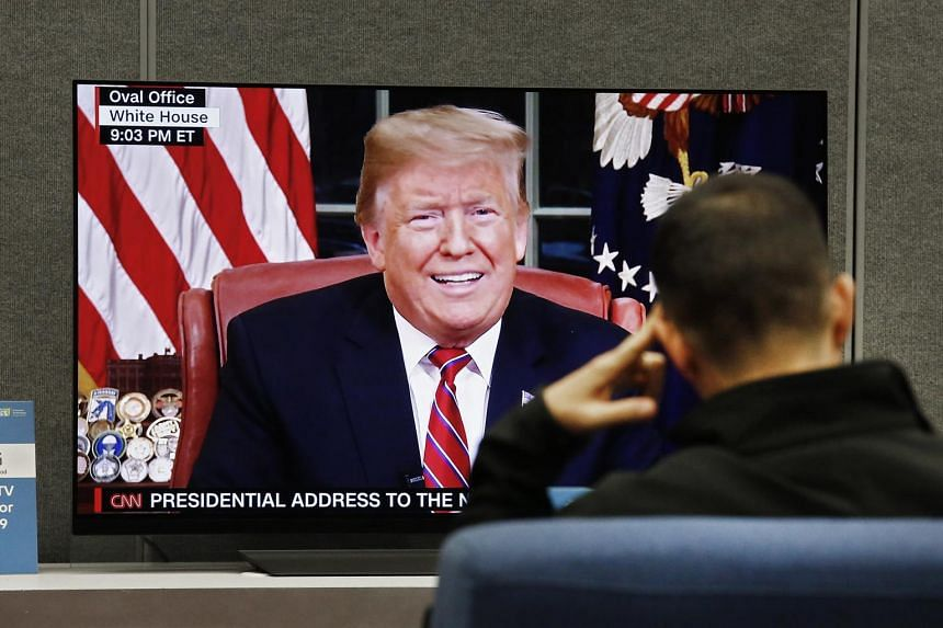 A man watches US President Donald Trump addressing the nation on TV in Las Vegas, Nevada, on Jan 8, 2019.
