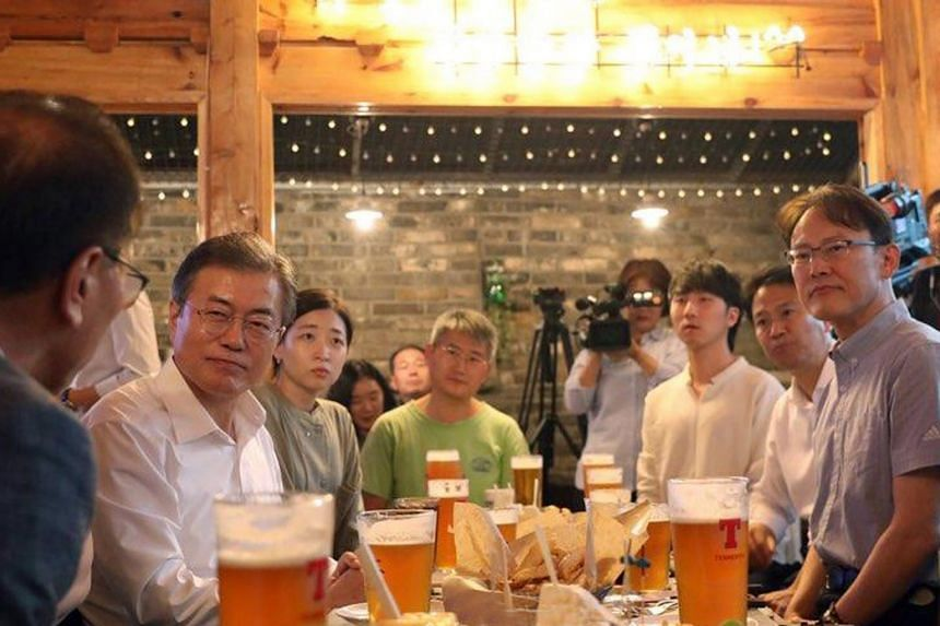 South Korean President Moon Jae-in (second from left, in white shirt) listening to concerns about minimum wage hike from a group of 30 people gathered at a pub in Gwanghwamun in Seoul, on July 26, 2018.