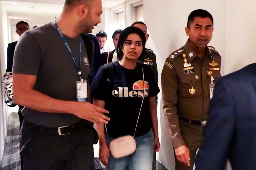 Ms Qanun (centre) being escorted by a Thai immigration officer (right) and United Nations High Commissioner for Refugees (UNHCR) officials at Suvarnabhumi international airport in Bangkok.