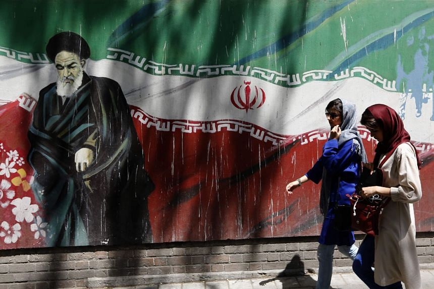 Iranians walk by a mural of the founder of the Islamic Republic Ayatollah Ruhollah Khomeini on the wall of the former US embassy in the Iranian capital Teheran.