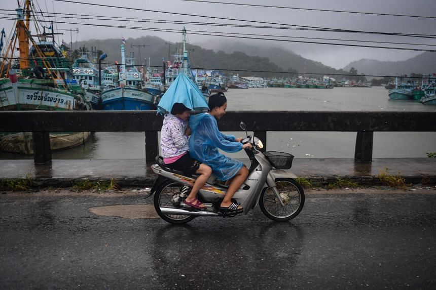 Two girls riding through heavy rain due to Tropical Storm Pabuk in the southern Thai province of Nakhon Si Thammarat, on Jan 4, 2019.