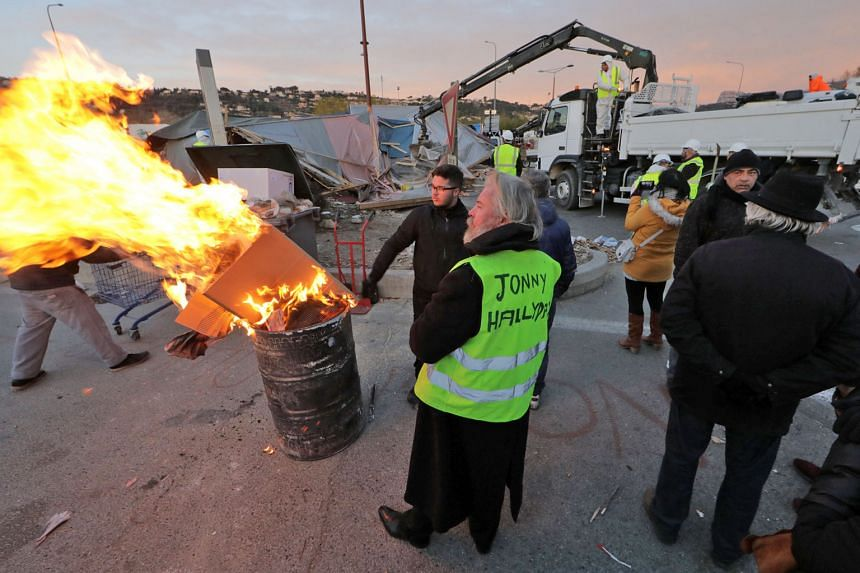 A yellow-vest protester and his comrades watching the dismantling of a yellow-vest camp installed at a roundabout in Nice, France, yesterday.