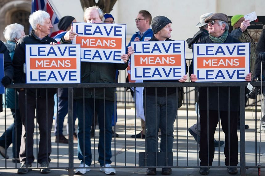 Pro-Brexit activists hold up placards outside the Houses of Parliament in London on Jan 8, 2019.