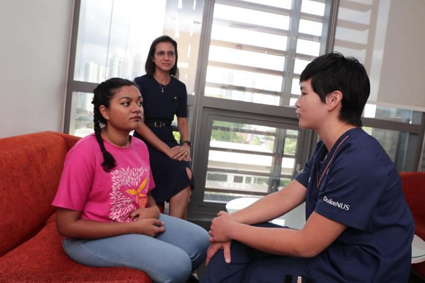 (From Left) Ms Masturah Oli, 22, simulated patient from Buds Theatre; Dr Kumudhini Rajasegaran, 45, Head and Senior Consultant, KK Women's and Children Hospital; and Ms Cheryl Woo, 28, medical student from Duke-NUS, in an adolescent simulated patie