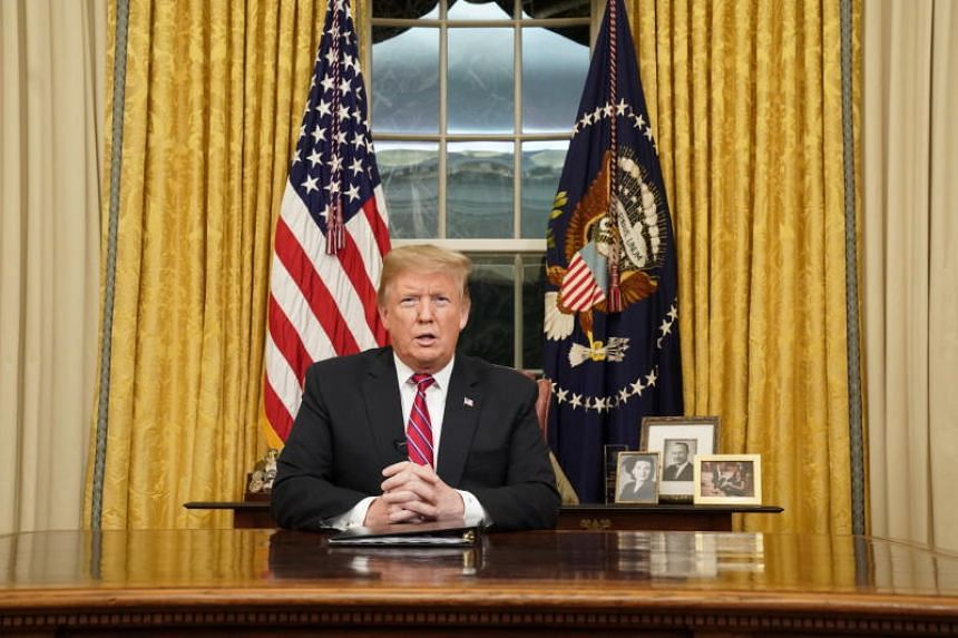 US President Donald Trump addressing a national television audience from behind his desk in the Oval Office of the White House in Washington, DC, on Jan 8, 2019.