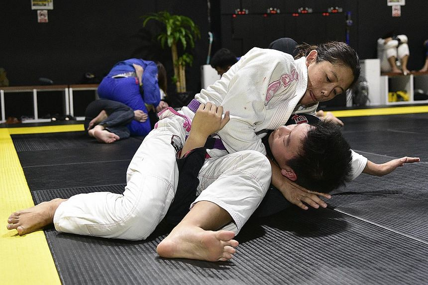 Former national swimmer May Ooi (in white) has been a professional mixed martial arts fighter since 2014.