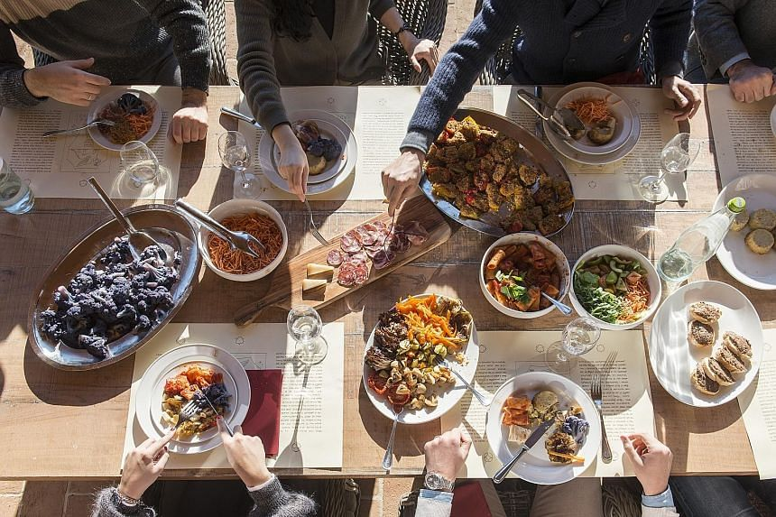 At Italian designer Brunello Cucinelli's headquarters in Solomeo, Italy, employees tuck into a multi-course lunch (above) for a nominal fee. LinkedIn, which does not charge for food even in its cafeterias, also provides several halal-meat options to