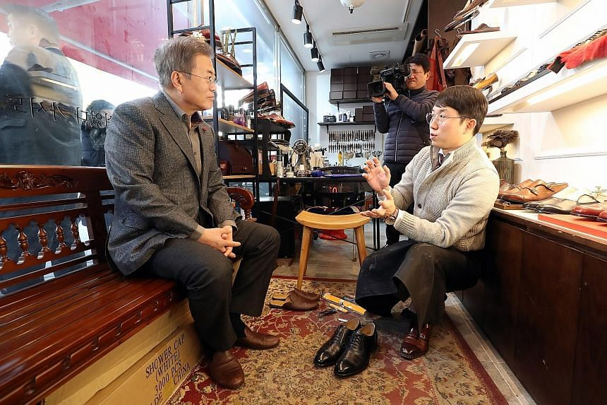 "South Korean President Moon Jae-in (left) talking to the owner of a shoe shop in Seoul last week while having his shoes made. Mr Moon had pledged to be a ""Gwanghwamun President"" with his office in downtown Seoul instead of the secluded Blue House, to"