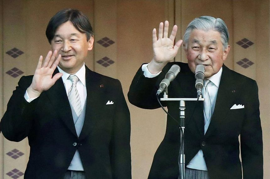 Japan's Emperor Akihito (right) and Crown Prince Naruhito wave to a crowd during the New Year's greeting ceremony at the Imperial Palace in Tokyo, on Jan 2, 2019.