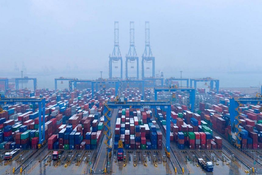 Containers and trucks seen at an automated container terminal in Qingdao port, Shandong province, China, on Dec 10, 2018.