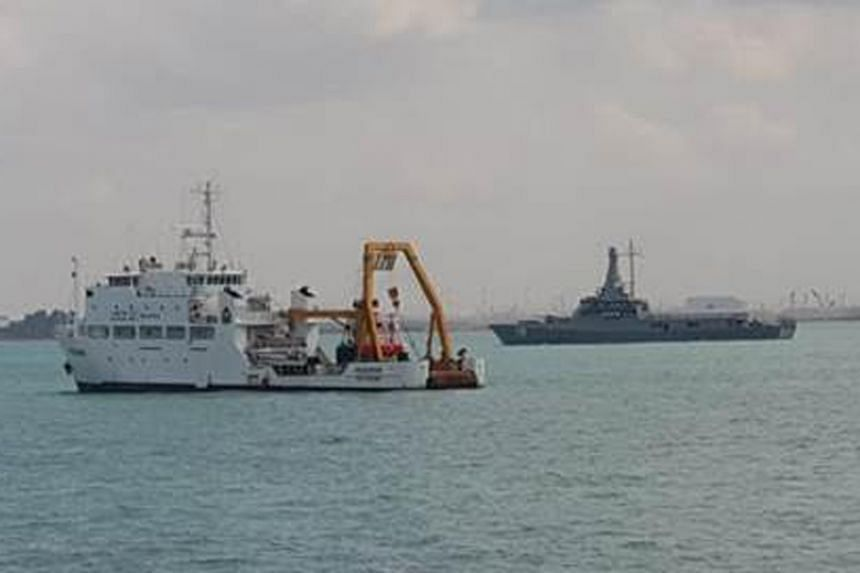 RSN Littoral Mission Vessel RSS Justice (background) keeping a close watch over Malaysia Marine Department vessel Pedoman (foreground) anchored in Singapore port limits.