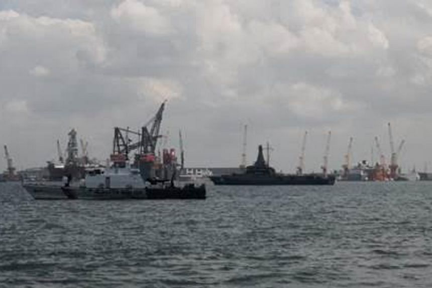 RSN Littoral Mission Vessel RSS Justice (right) keeping a close watch over Malaysian Maritime Enforcement Agency vessel KM Marudu (left) anchored in Singapore port limits.