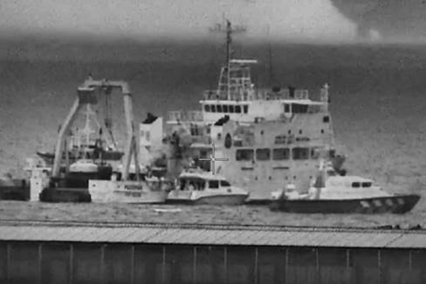 A Police Coast Guard vessel (right) issuing violation calls against Malaysia Marine Department (MMD) Pedoman (background) and MMD vessel Tanjung Puteri (centre), which intruded into Singapore's territorial waters off Tuas.