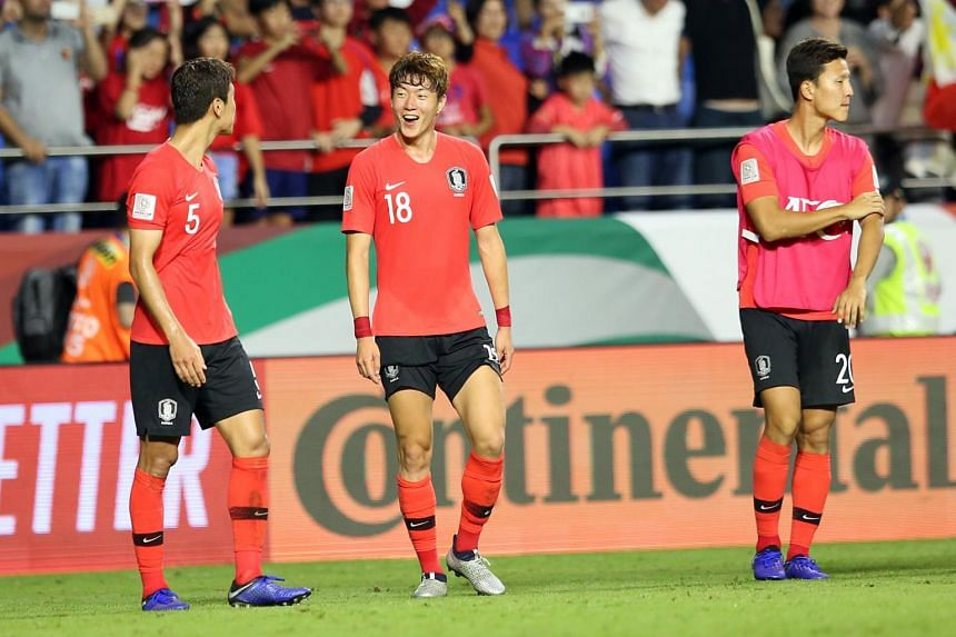 Hwang Uijo (centre) and Jung Wooyoung (left) of South Korea react after winning the 2019 AFC Asian Cup group C preliminary round match on Jan 7, 2019.