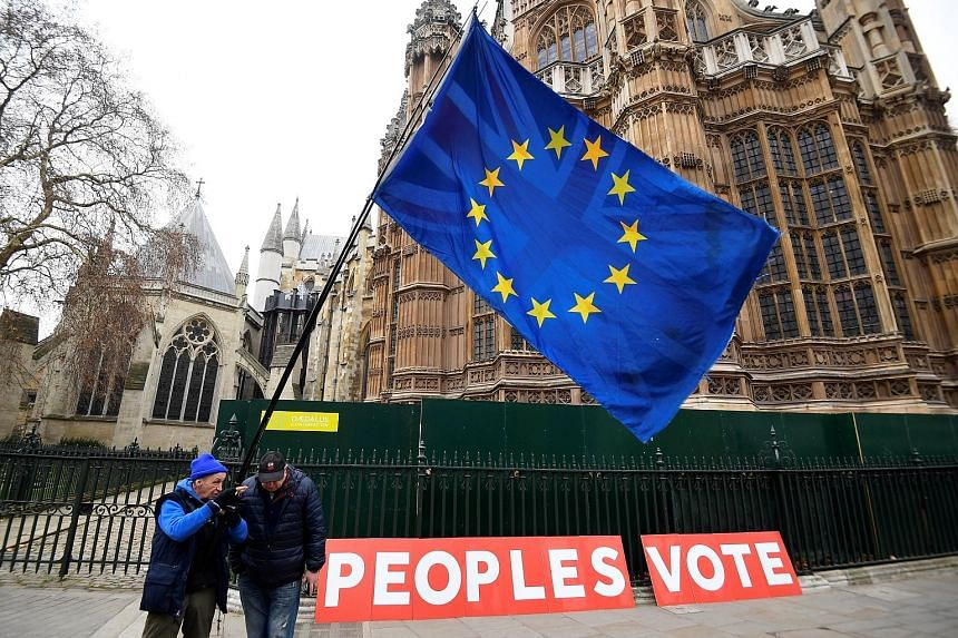 Anti-Brexit protesters waving the EU flag outside the Houses of Parliament in London yesterday. If the UK tumbles out of the bloc on March 29 without any new trading partnership in place, official analysis suggests the impact could trigger a recessio
