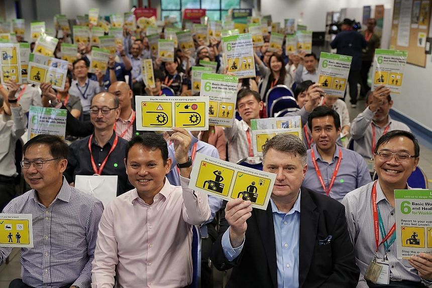 (From left) WSH Council chairman John Ng, Minister of State for Manpower Zaqy Mohamad and SAESL CEO Bill Wozniak holding up workplace safety reminder stickers.