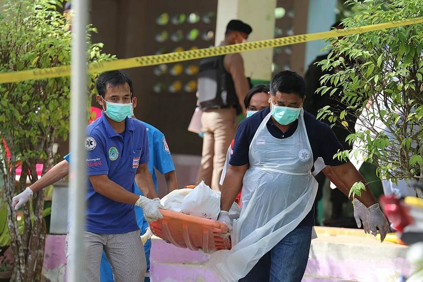 Paramedics taking away the body of one of the four Thai civil defence volunteers who were shot and killed outside a school in the southern province of Pattani yesterday.