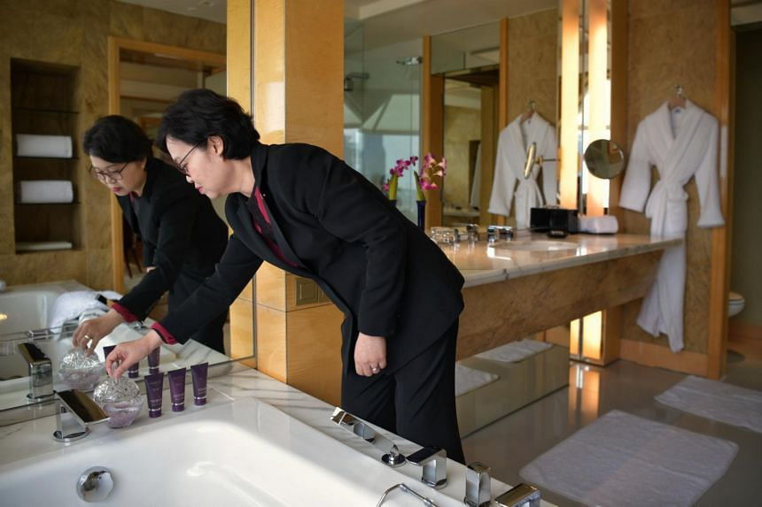 Ritz-Carlton's executive housekeeper Low Chee Mung cleaning a room.