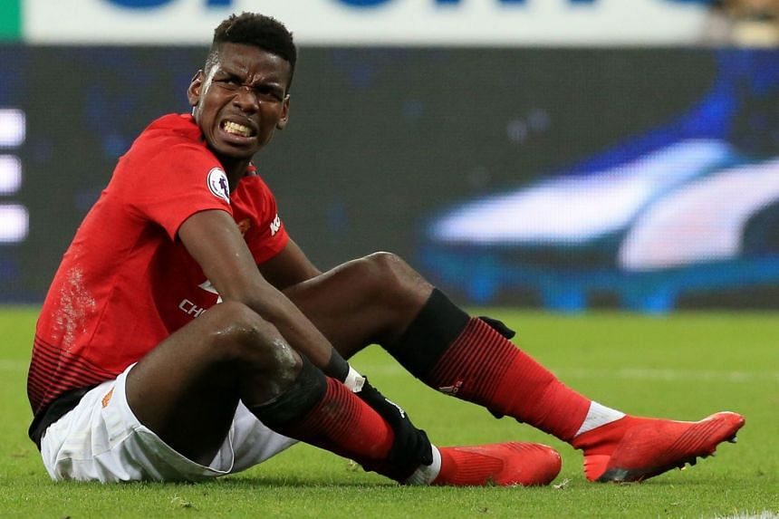 Pogba holds his leg following a challenge during the match against Newcastle United.