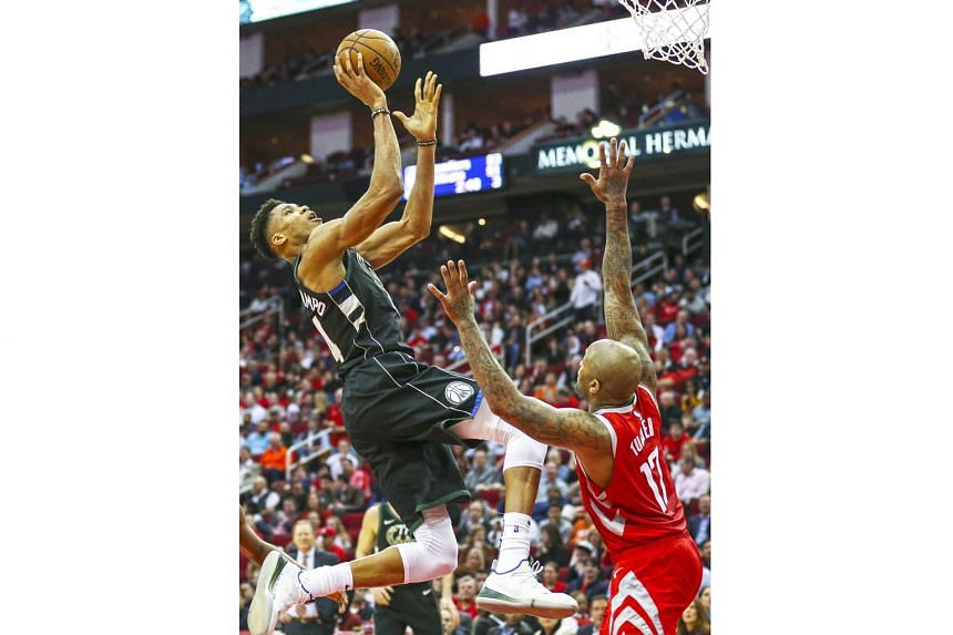 Milwaukee Bucks' Giannis Antetokounmpo driving to the basket against the Houston Rockets' P.J. Tucker in the third quarter on Wednesday. The Bucks forward tipped in a basket with 39.1 seconds left to help the team with the best National Basketball As