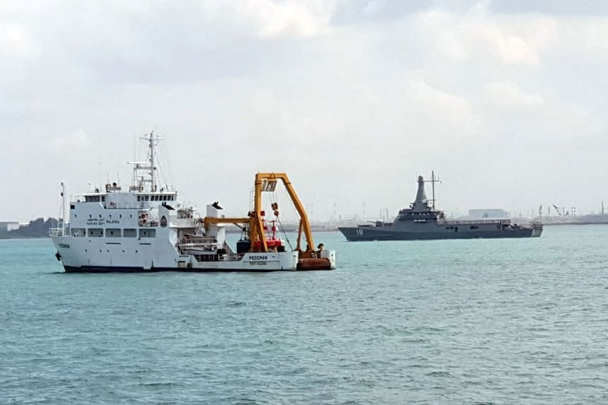 Republic of Singapore Navy littoral mission vessel RSS Justice (at right) and the Malaysian Marine Department vessel MV Pedoman (foreground), which was anchored within Singapore port limits.