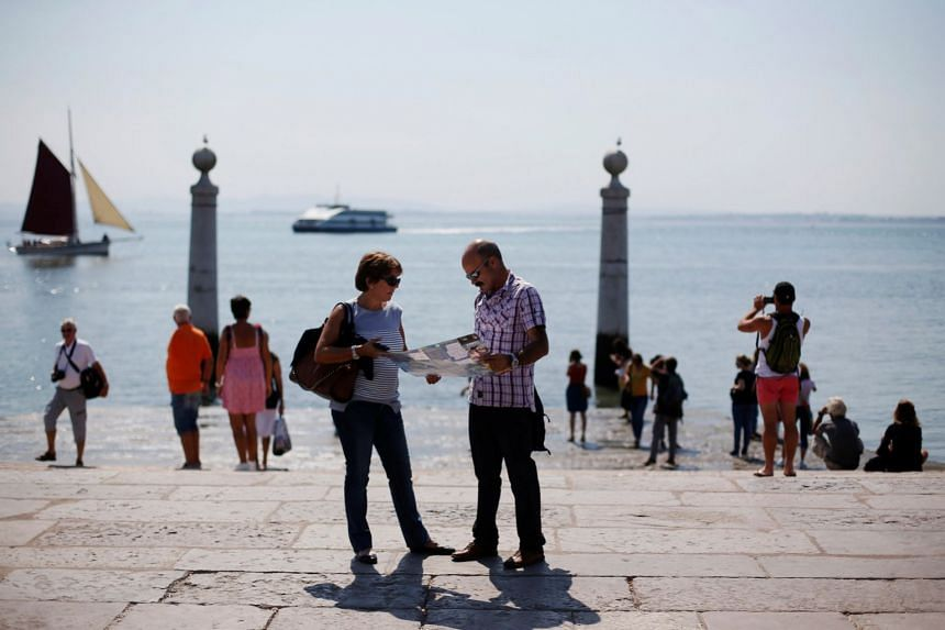 Tourists visit the Columns Pier in front of the Tagus River in Lisbon in a 2013 file photo.