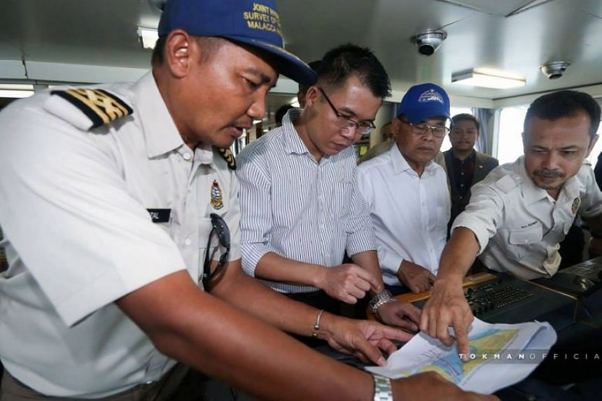 Mr Osman (centre, in blue cap) and state exco member Tan Hong Pin (second from left) visiting crew on board MV Pedoman, in a photo Mr Osman posted on his Facebook page.