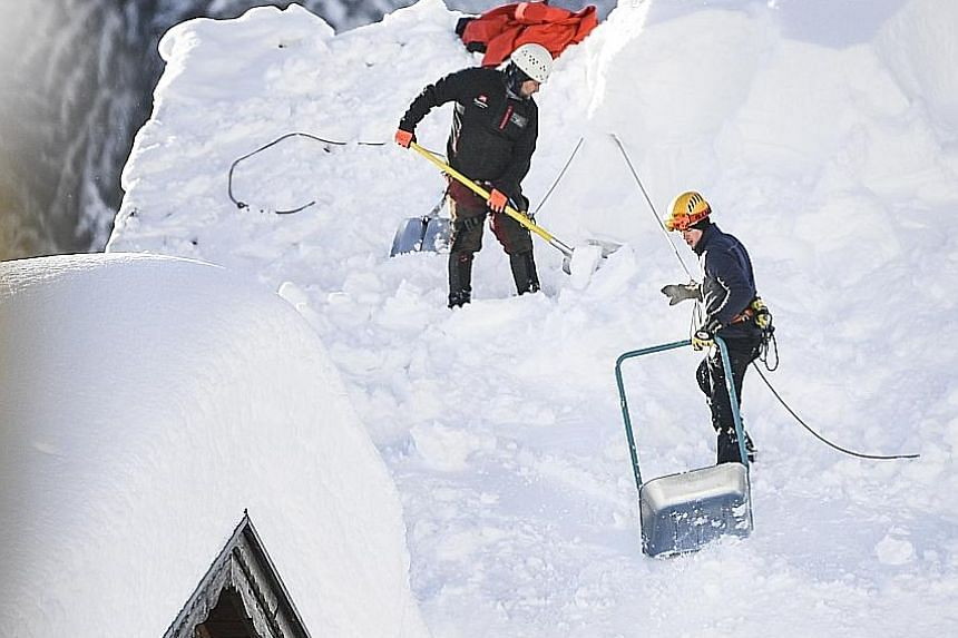 Workers clearing a roof in the town of Gerold, in Germany, following heavy snowfall.