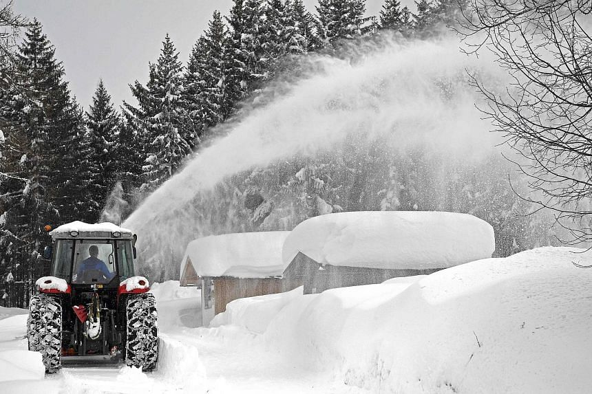 German army soldiers clearing snow from the roof of a grammar school in Berchtesgaden, Germany. Drivers in Untertauern, Austria, putting snow chains on their car tyres on Monday as the authorities in Austria and southern Germany close roads because o